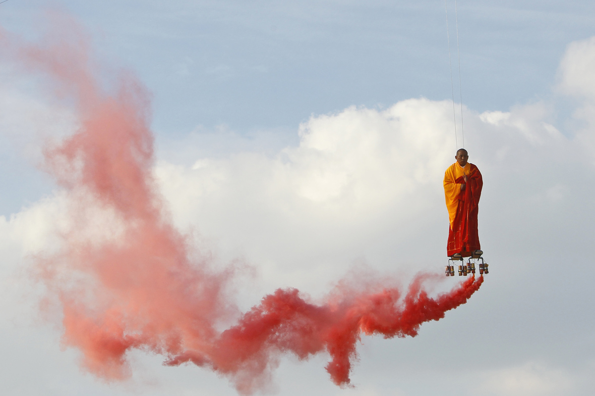 Suspended by wires, Chinese artist Li Wei performs in the sky  at La Villette in Paris