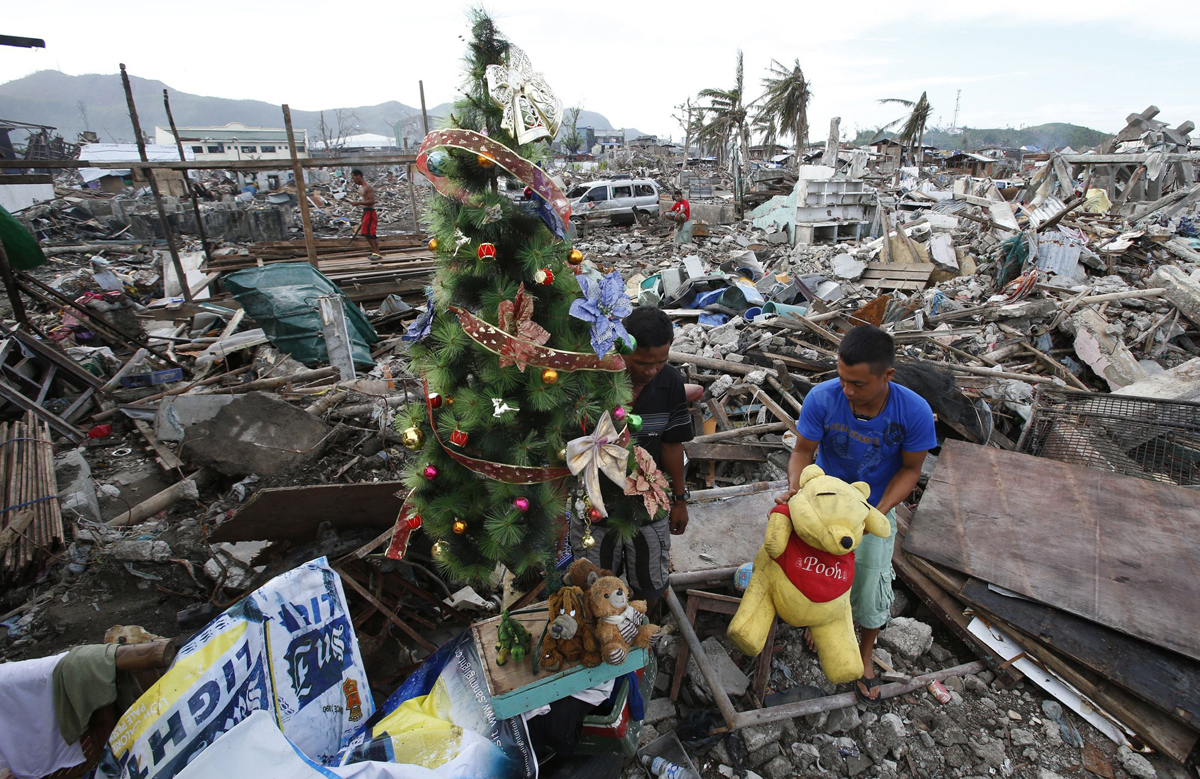 A typhoon survivor decorates a Christmas tree amidst the rubble of destroyed houses in Tacloban city