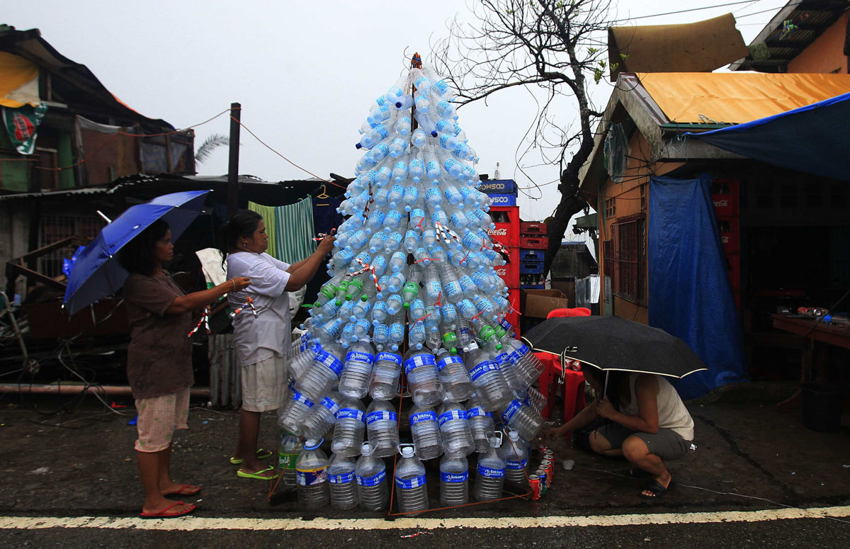 Victims of super Typhoon Haiyan decorate their improvised Christmas tree with empty cans and bottles at the ravaged town of Anibong