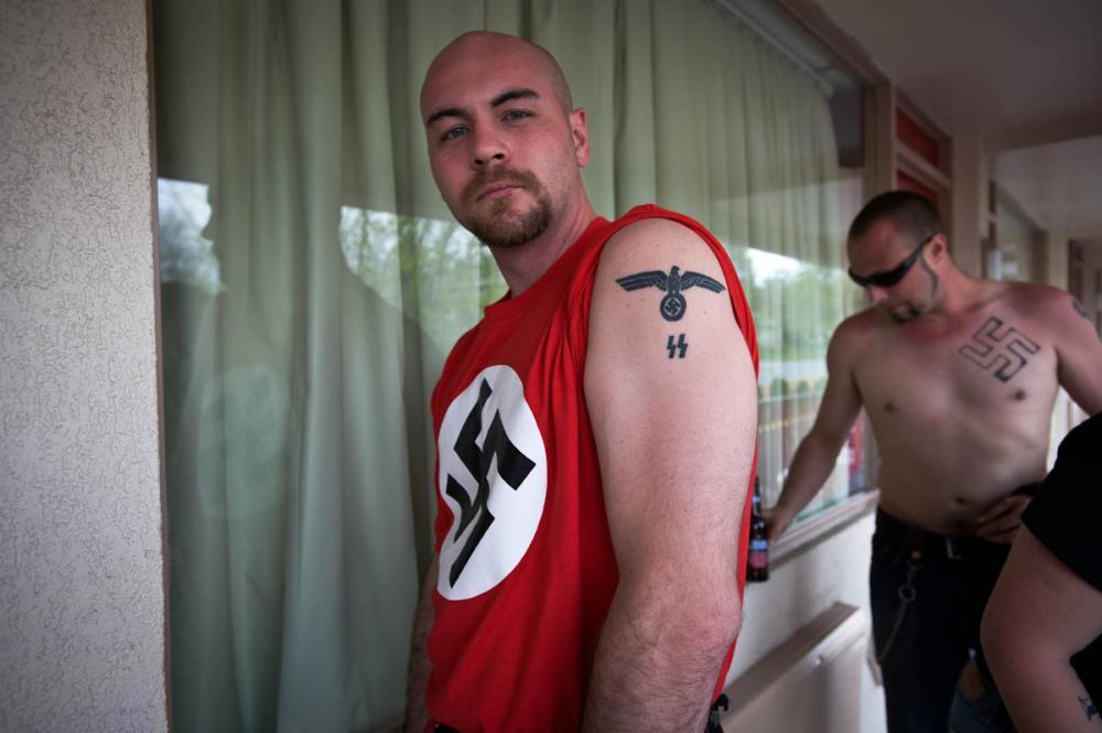 Člen NSM ukazuje své tématické tetování.